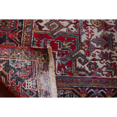 6 - An antique Heriz carpet with central geometric medallion, on a red and cream ground, contained by ge...