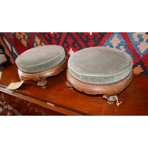 133 - A pair of Victorian Aesthetic carved walnut footstools with stud bound green velour upholstery on fo...