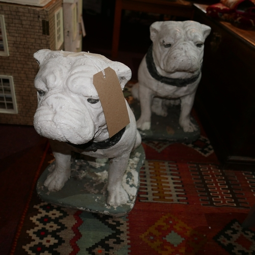 165 - A pair of white painted stone bull dogs...