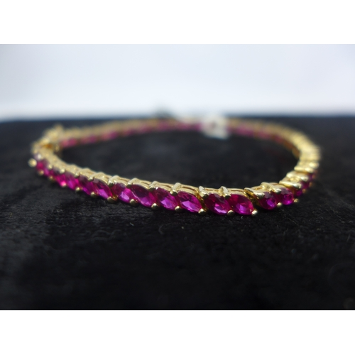 1003 - An 18ct yellow gold natural ruby tennis bracelet, claw-set with fifty-two marquise-shaped faceted ru...