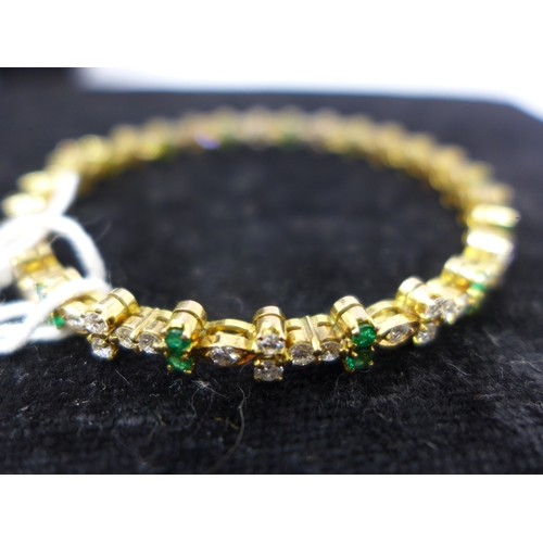 1006 - An 18ct yellow gold diamond and emerald bracelet, composed of alternating double emeralds and diamon...