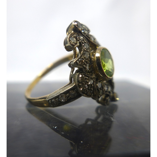 1014 - A Belle Epoque yellow gold, diamond and peridot ring, the central round bezel-set peridot framed by ...