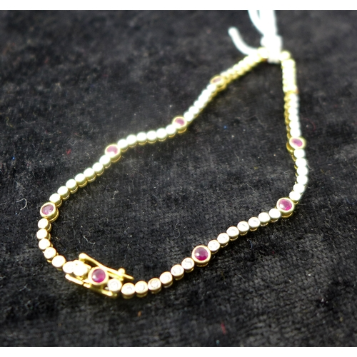 1017 - A boxed ladies 18ct yellow gold tennis bracelet inset with sixty-five collet-set round brilliant-cut...