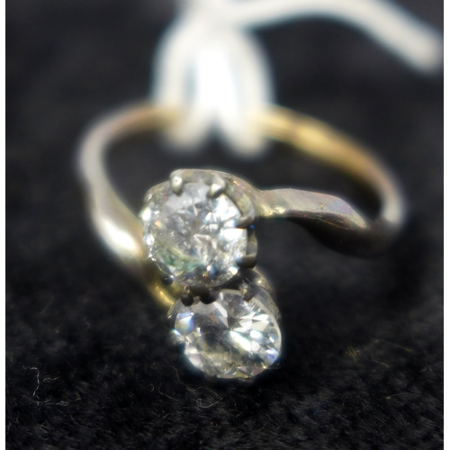 1030 - An antique yellow gold double diamond crossover ring, inset with two brilliant cut diamonds in claw ...