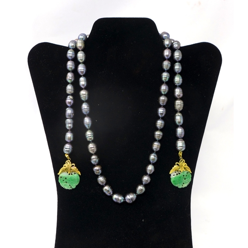 1012 - A long grey freshwater pearl larius necklace with high carat yellow gold and carved, circular green ...