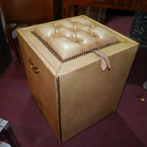 256 - An early 20th century stud bound leather clad ottoman, with button down leather upholstered seat/lid...