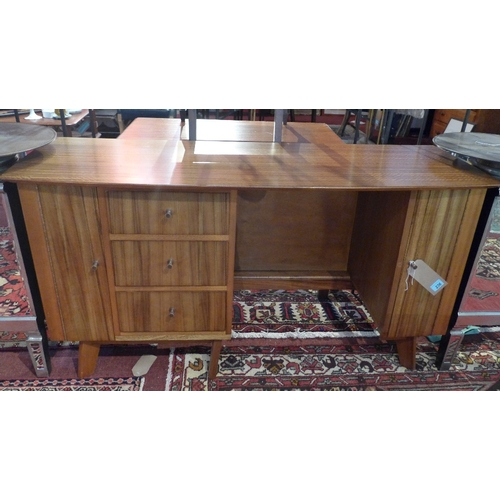 348 - A mid century teak desk, with a shaped top over an arrangement of drawers and cupboard doors on spla...