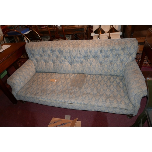 243 - An early 20th century three seater sofa, with floral button back upholstery raised on turned feet...