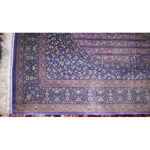 6 - A Qum silk carpet with central floral medallion, on a purple ground, contained by floral motifs and ...