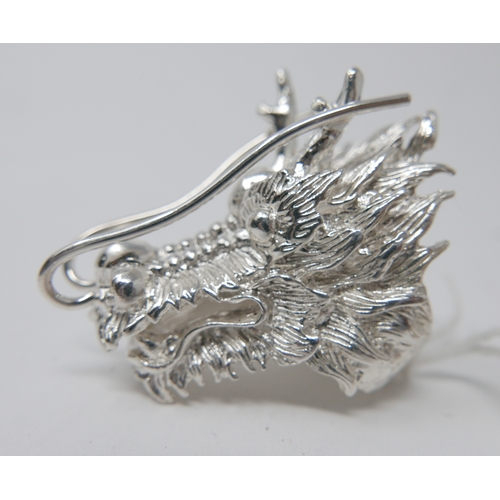 120 - A large and weighty ring in the form of a ferocious dragon head with textured detailing, ring size: ...