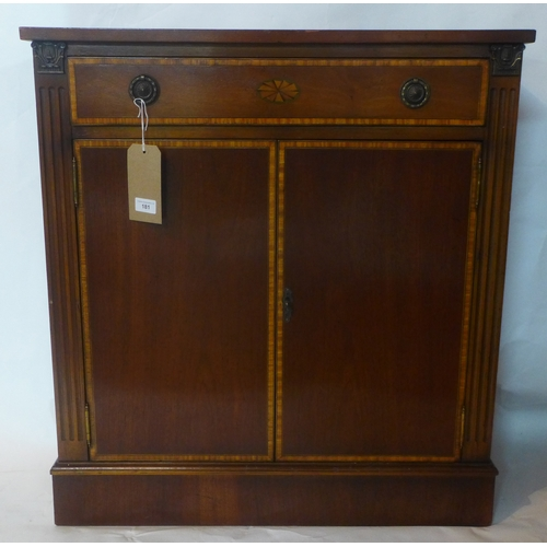 181 - A 20th century inlaid mahogany side cabinet, with single drawer over two cupboard doors, raised on s...