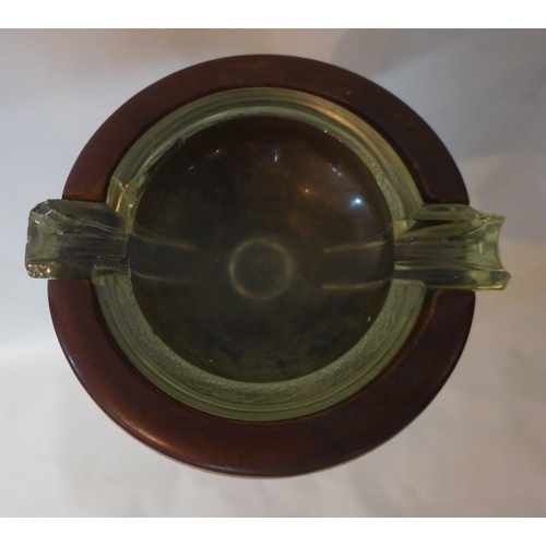 250 - An early 20th century oak floor standing ashtray, with glass insert, raised on stepped circular base...