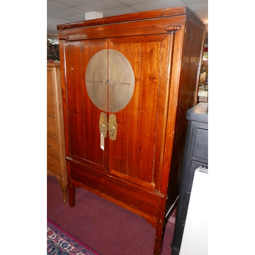 205 - A Chinese hardwood and brass mounted wedding cabinet, having two cupboard doors with central circula...