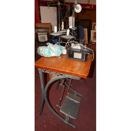 234 - A Willcox & Gibbs overlock sewing machine, set on oak top with a lamp above cast metal supports and ...