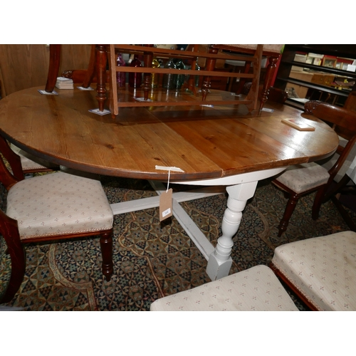 255 - A 20th century circular pine dining table, with white painted base and extra leaf...