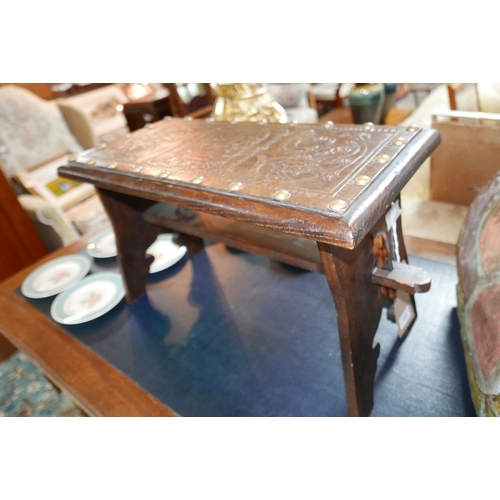 253 - An early 20th century oak prayer stool, with brass studded leather clad top decorated with ship cres...