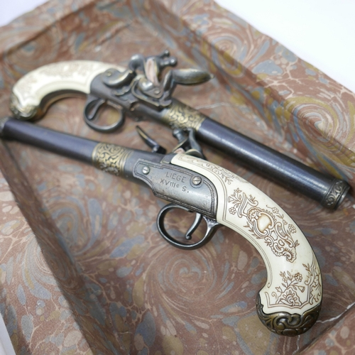 16 - A pair of reproduction flintlock pistols enclosed in a hollowed out antique French encyclopedia...