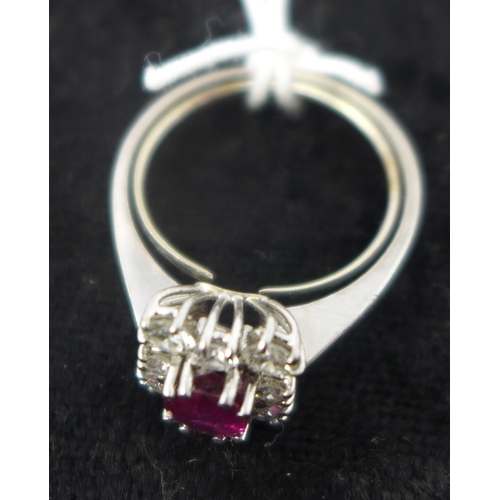 5 - An 18ct white gold, natural ruby and diamond cluster ring, the central oval faceted ruby in a six-cl...
