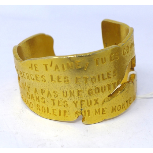 26 - A Lancome, Paris, 'Poeme' large and weighty gilt metal cuff bracelet adorned with a French love poem...
