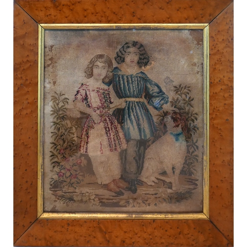 17 - An 18th century needlework embroidery depicting two children and their dogs amongst flowers, in glaz...
