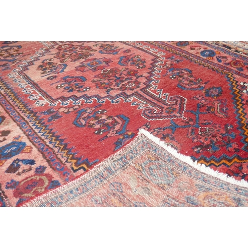 110 - A Turkish rug with geometric floral medallion, on a red ground, contained by geometric border, 200 x...