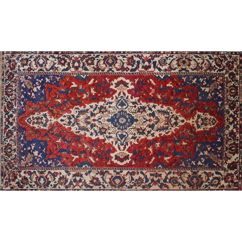 68 - A Persian Bakhtiari carpet, central double medallion with repeating pendent petal motifs on a terrac...