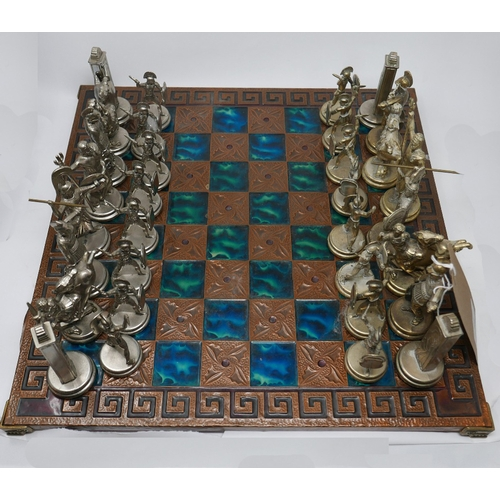 86 - A 20th century Greek chess set, with brass pieces on a copper clad board...