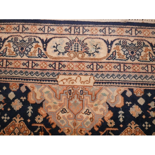 345 - A signed Nepalese carpet with geometric floral motifs, on a blue ground, contained by floral border ...