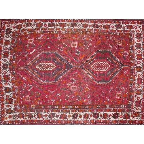 374 - A Shiraz carpet with twin pole medallion surrounded by geometric motifs, on a red ground, contained ...