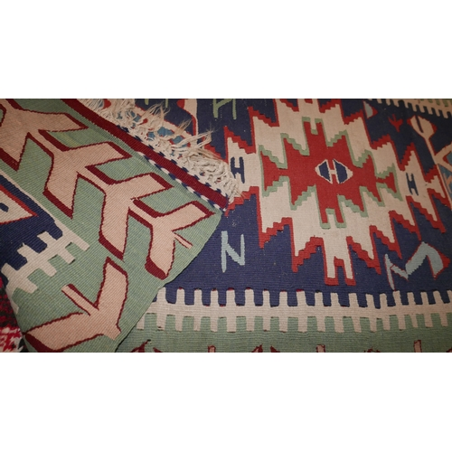 376 - A Turkish kelim runner with four geometric medallion, on a blue ground contained by geometric border...