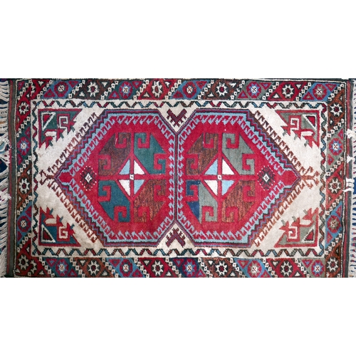 378 - A Turkish rug with two geometric medallions, on a red and cream ground, contained by geometric borde...