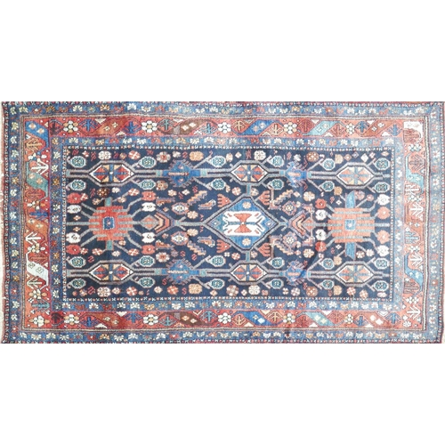 112 - A North West Persian Nahavand rug, central pole medallion with repeating petal motifs on a sapphire ...