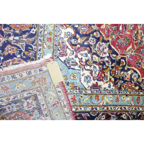 70 - A Persian Kahsan carpet, central double pendent medallion with repeating spandrels on a rouge field,...