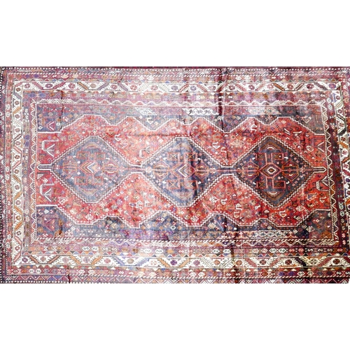 76 - A South West Persian Qashqai carpet, triple pole medallion with repeating petal motifs on a terracot...