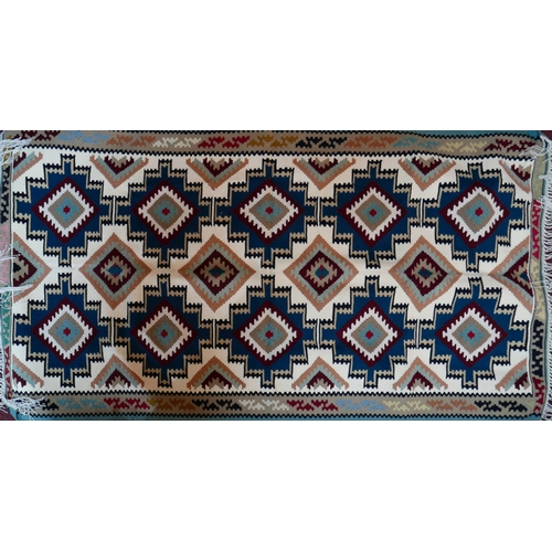 35 - A Persian kelim woolen rug composed of a repeating geometric design in shades of blue, teal, maroon,...