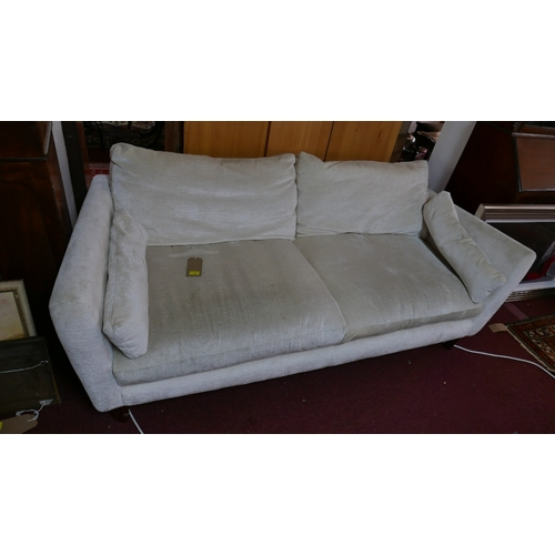 15 - A large twin seater sofa by Laura Ashley upholstered in cream velvet with matching cushions, on four...