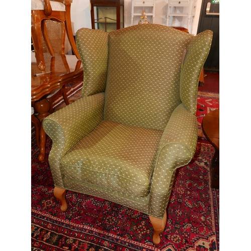 50 - A contemporary wing back armchair in green and gold upholstery raised on beech wood legs...