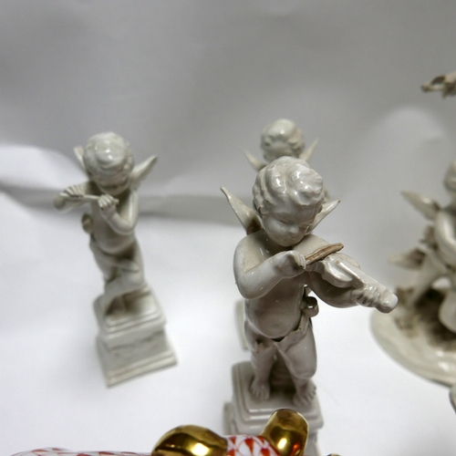 59 - A collection of Capodimonte white glazed cherubs, each playing musical instruments, consisting of si...