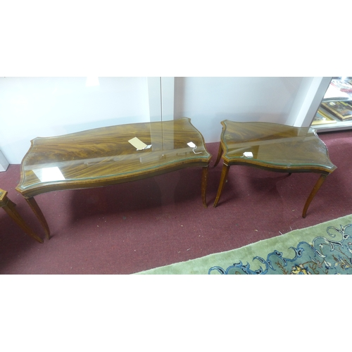 29 - A 20th century mahogany serpentine coffee table with a pair of matching side tables...