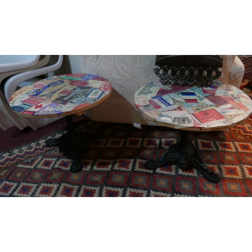 398 - A pair of low circular tables on wrought iron bases and Parisian scenes to the top. D.56cm...