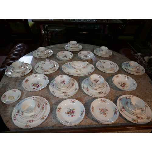 73 - A large dinner service with a white ground decorated with a floral pattern comprising of a large ser...