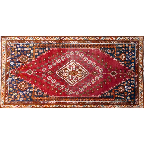 96 - A South West Persian Qashqai rug, central diamond medallion with repeating petal motifs on a terraco...