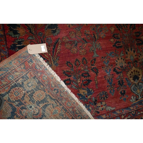 136 - A large 20th century Sarouk carpet, with repeating floral motifs on a red and blue ground, contained...