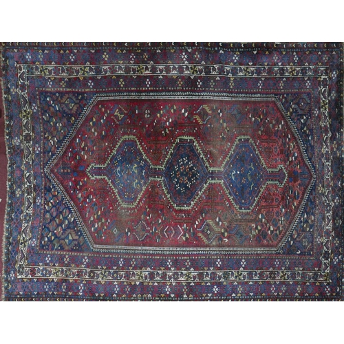 62 - An antique Qashqai carpet with triple pole diamond medallion, within a lozenge field, on a red and b...