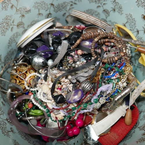 65 - A large circular box containing a variety of costume jewellery to include earrings, necklaces, brooc...