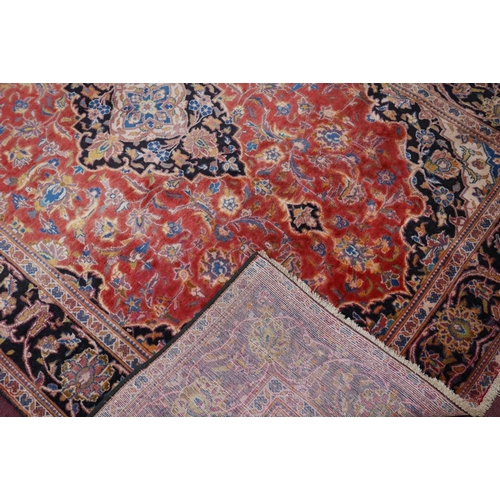 66 - A Central Persian Kashan rug, central double pendent medallion with repeating petal motifs on a roug...