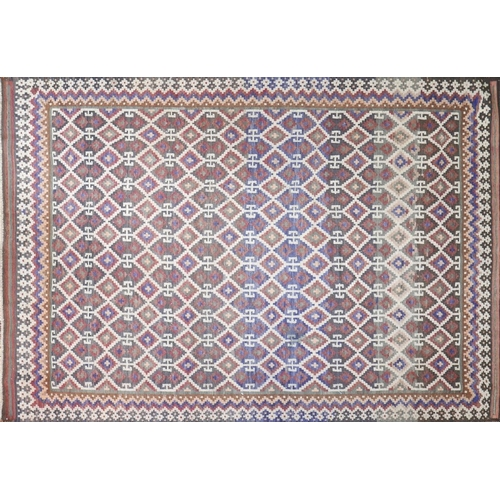 71 - A South Persian Qashqai kilim carpet, repeating lattice motifs all over a terracotta field, within s...