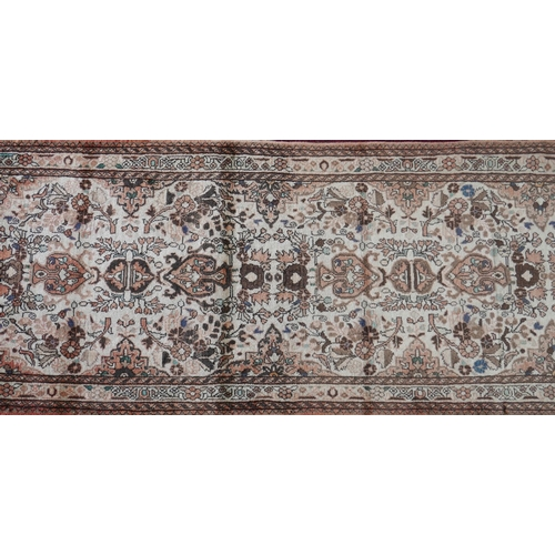 75 - A North West Persian Sarouk runner, repeating stylised floral motifs with repeating floral and anima...