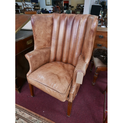 132 - An Eichholtz wingback chamberlain chair, with brown leather upholstery, raised on mahogany legs and ...