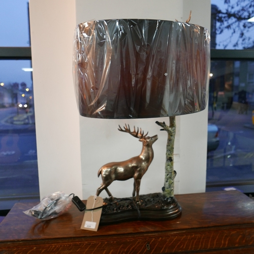220 - A contemporary lamp modelled as a stag by a tree, with oval shade, H.65 L.35cm...